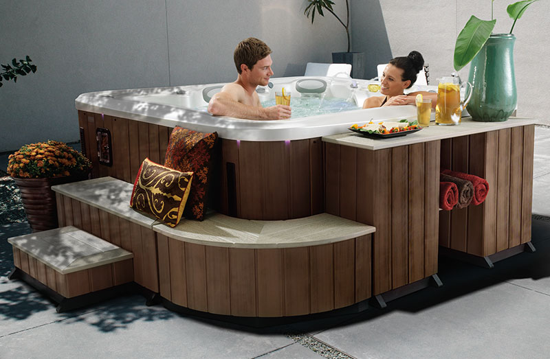Man and woman relaxing in hot tub with drinks in hand. Steps, benches, corner pieces and shelving unit display easy access into hot tub, as well as a counter to hold snacks and drinks and shelving hold towels nearby.