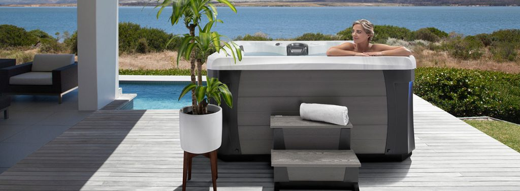 Woman sitting in hot tub leaning against edge with two steps outside the hot tub.