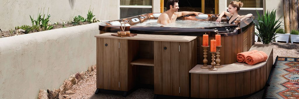 Man and woman sitting in hot tub, surrounded by cabinets, corner pieces and benches for easy access into the hot tub.