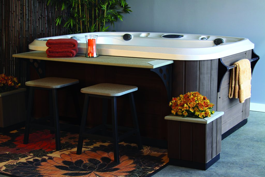 A counter top, is attached to an empty hot tub with stools beneath it, flower planter box. On the other side, a towel bar hands a single towel off the cabinet of the hot tub.