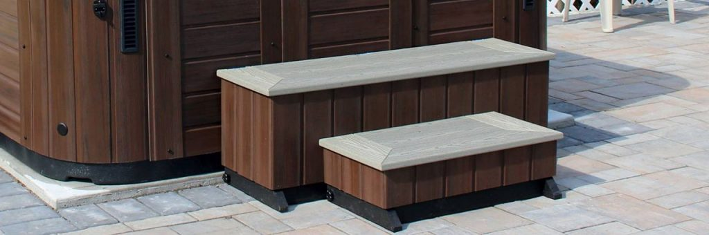 A tall bench stands in between hot tub edge and smaller step, providing steps into hot tub.