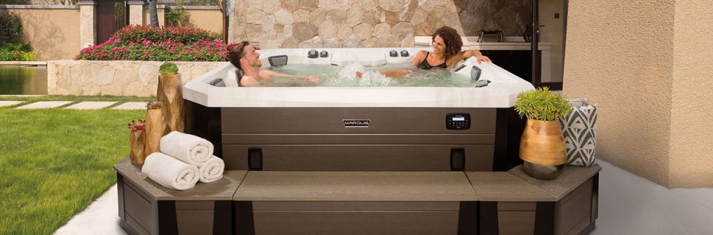Man and woman relaxing in hot tub, with benches and corner pieces providing easy access into hot tub. A flower pot and set of rolled towels sit on bench outside hot tub.