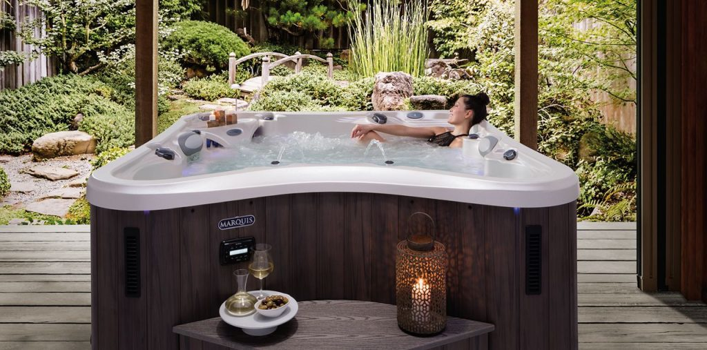 Woman sitting in hot tub with curved single bench in front of hot tub with a candle sitting on it.