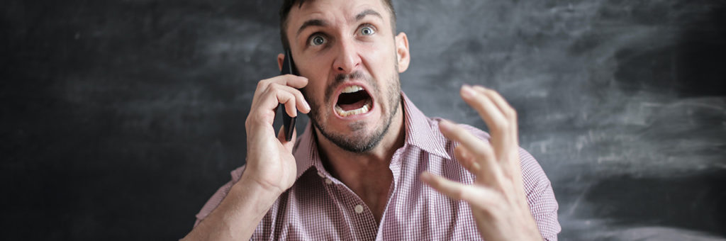 A frustrated man shouting into a mobile phone.