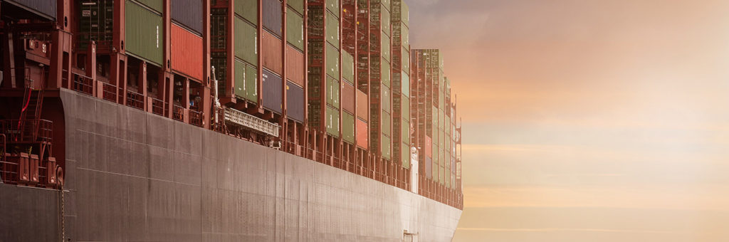 A container ship stacked high with containers, sailing on smooth seas, with sunshine on the horizon.