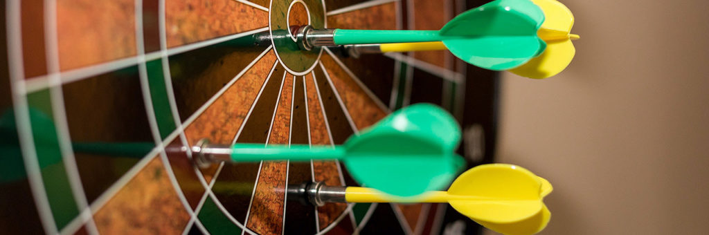 A dart board with multiples darts missing the bullseye.