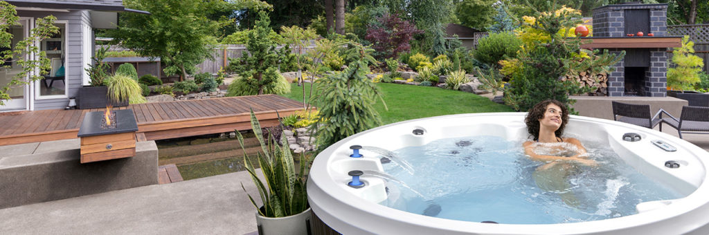 The same beautiful backyard with the open spot on the deck filled with a Marquis Monaco hot tub. A woman is soaking in the hot tub lounge with a smile on her face.
