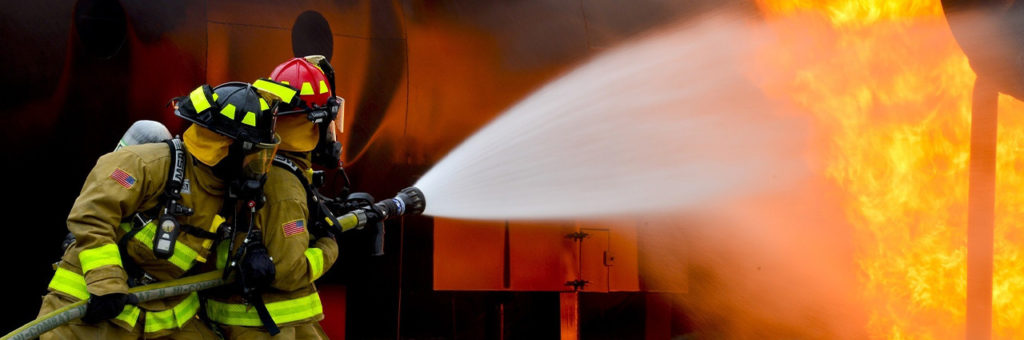 Two firefighters spray water on a raging industrial fire.