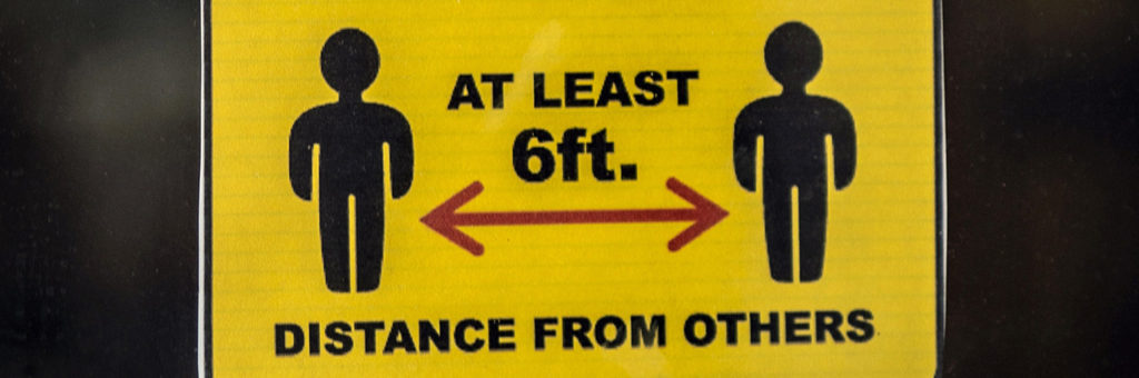 An industrial sign telling workers to maintain at least 6 feet of distance from others.
